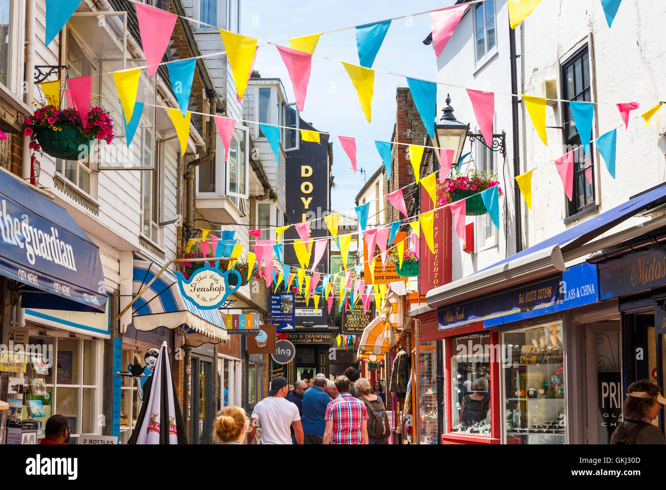 Street scene with colourful bunting and shop signs in The Lanes, Brighton, East Sussex, UK - Stock Image