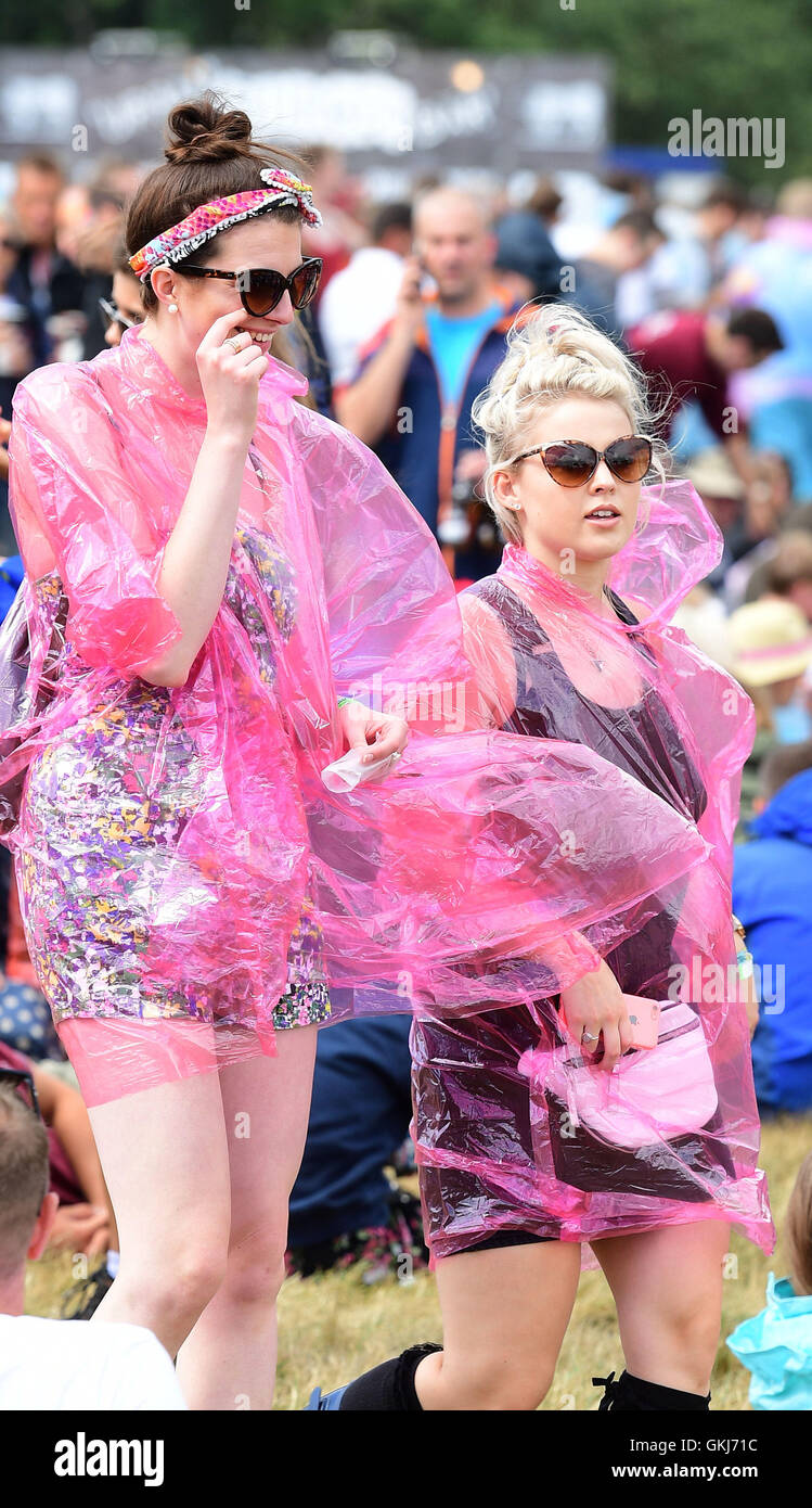 Festival goers wear ponchos at the V Festival at Hylands Park in Chelmsford, Essex. - Stock Image