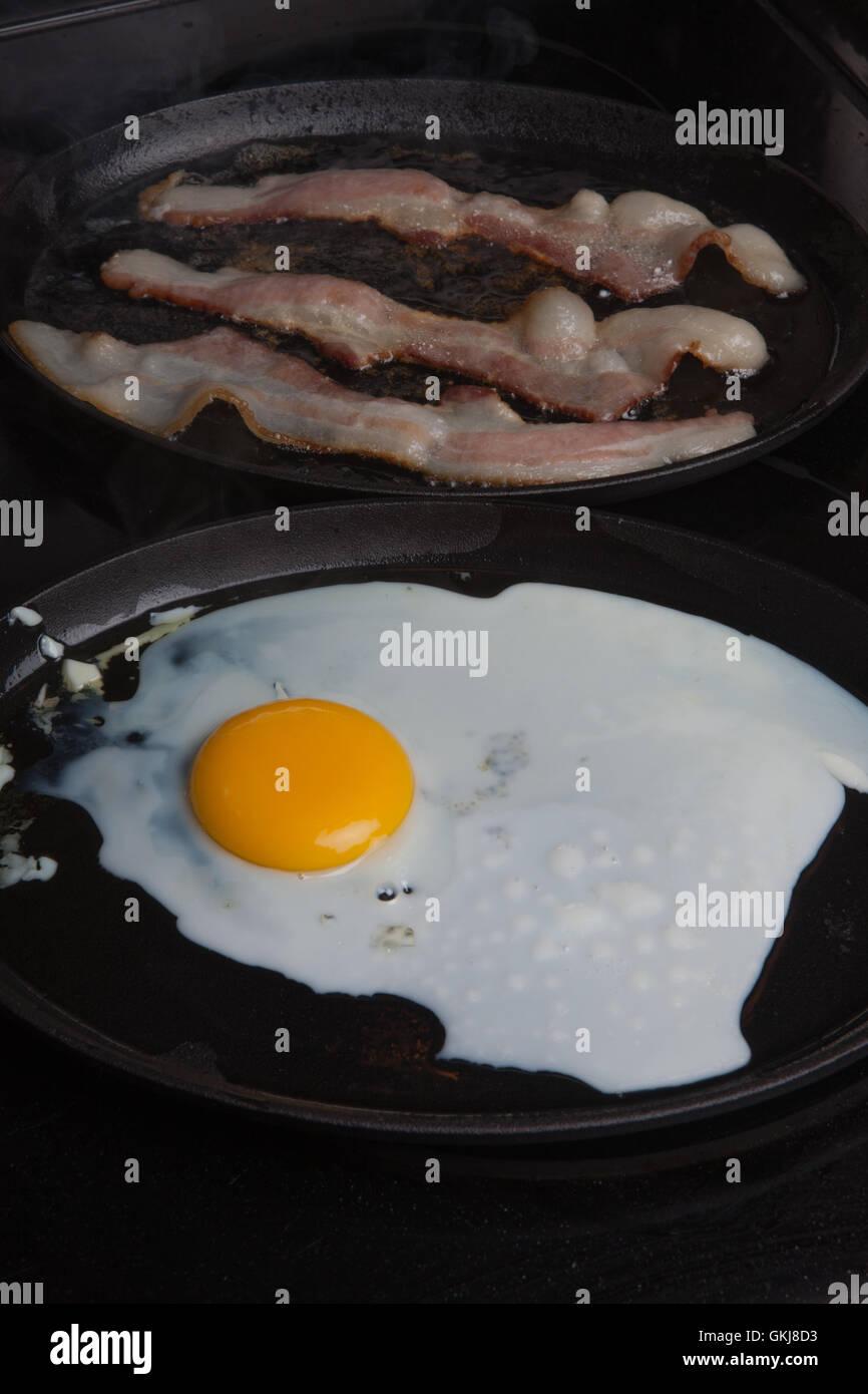 Fried egg,sunny side up yolk, yellow white, fried beacon,fat, pork, - Stock Image
