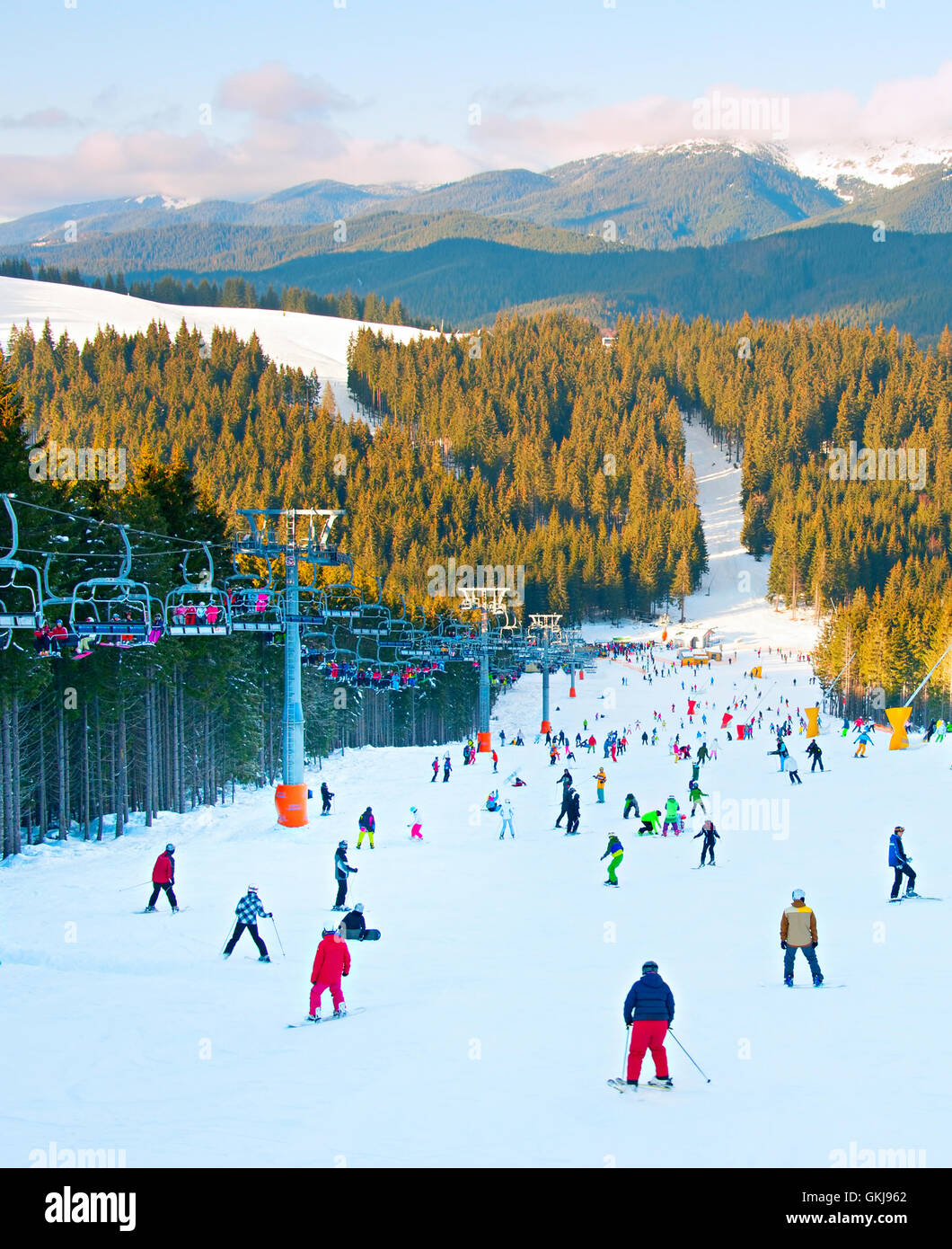 People skiing and snowboarding on a slope at ski resort - Stock Image