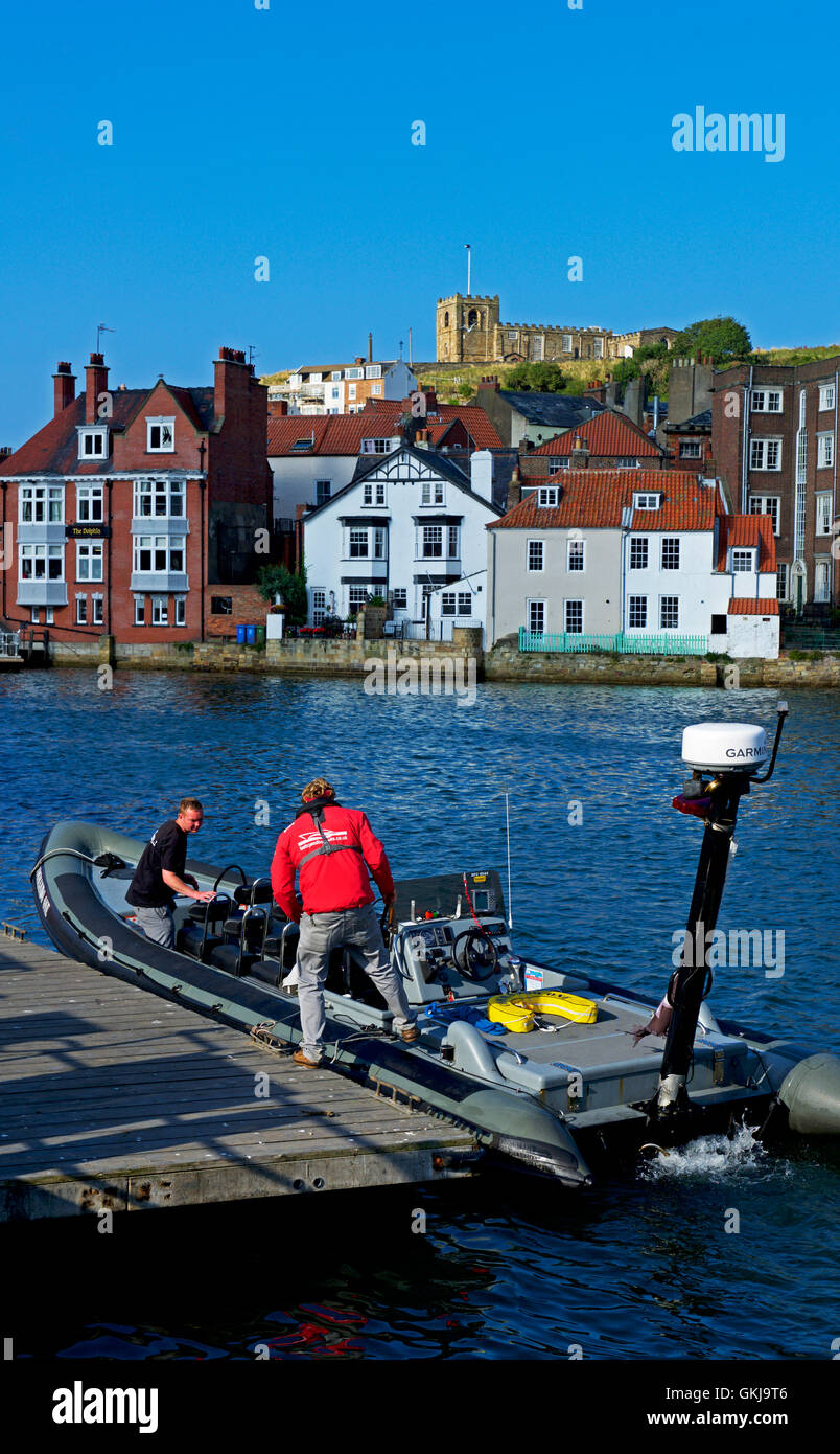 Two men with RIB in the harbour, Whitby, North Yorkshire, England UK - Stock Image
