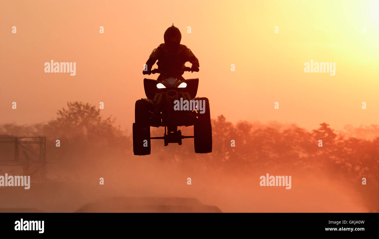 Silhouette ATV or Quad bikes Jump in the sunset. - Stock Image