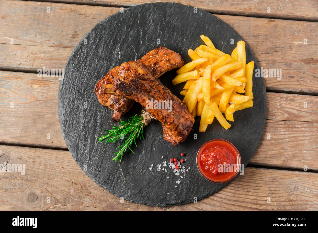 baked pork ribs with french fries and red sauce - Stock Image