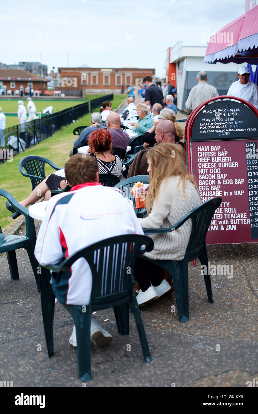 Holiday makers watching bowling outside cafe, Great Yarmouth - Stock Image