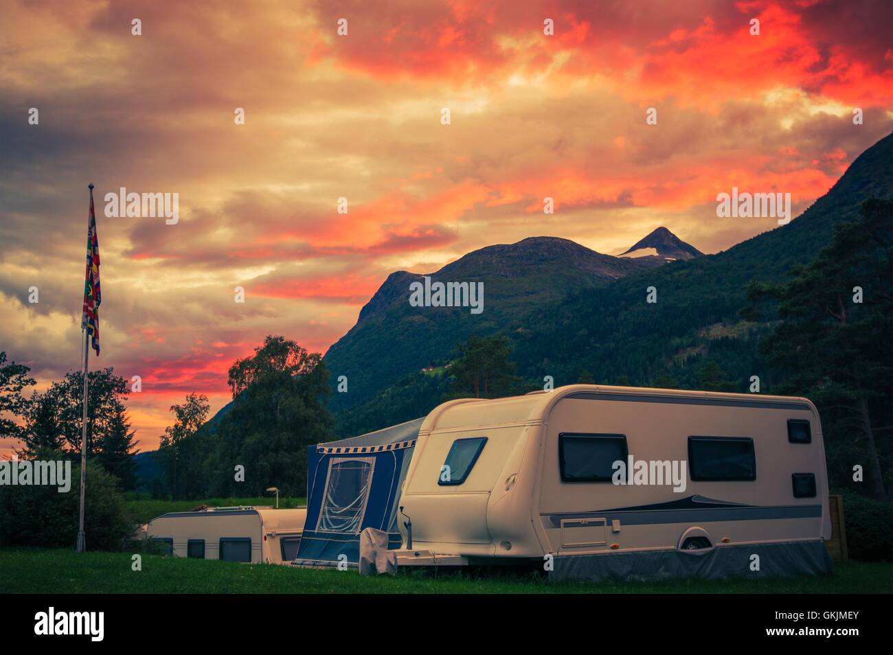 Scenic Camping Sunset. Sunset Sky Over Campground with Travel Trailers. Campsite Caravan Camping. - Stock Image