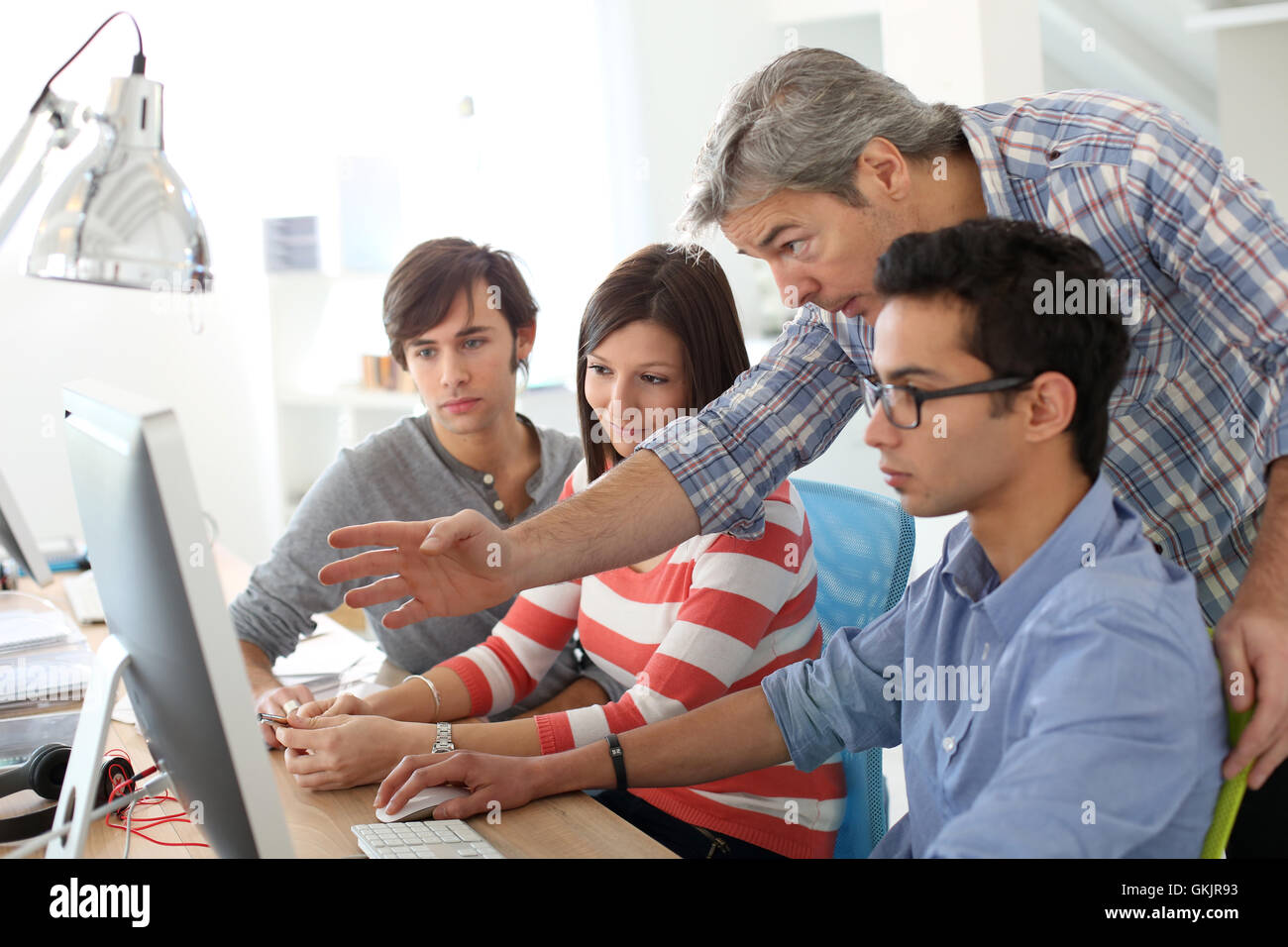 Teacher with students working on desktop - Stock Image
