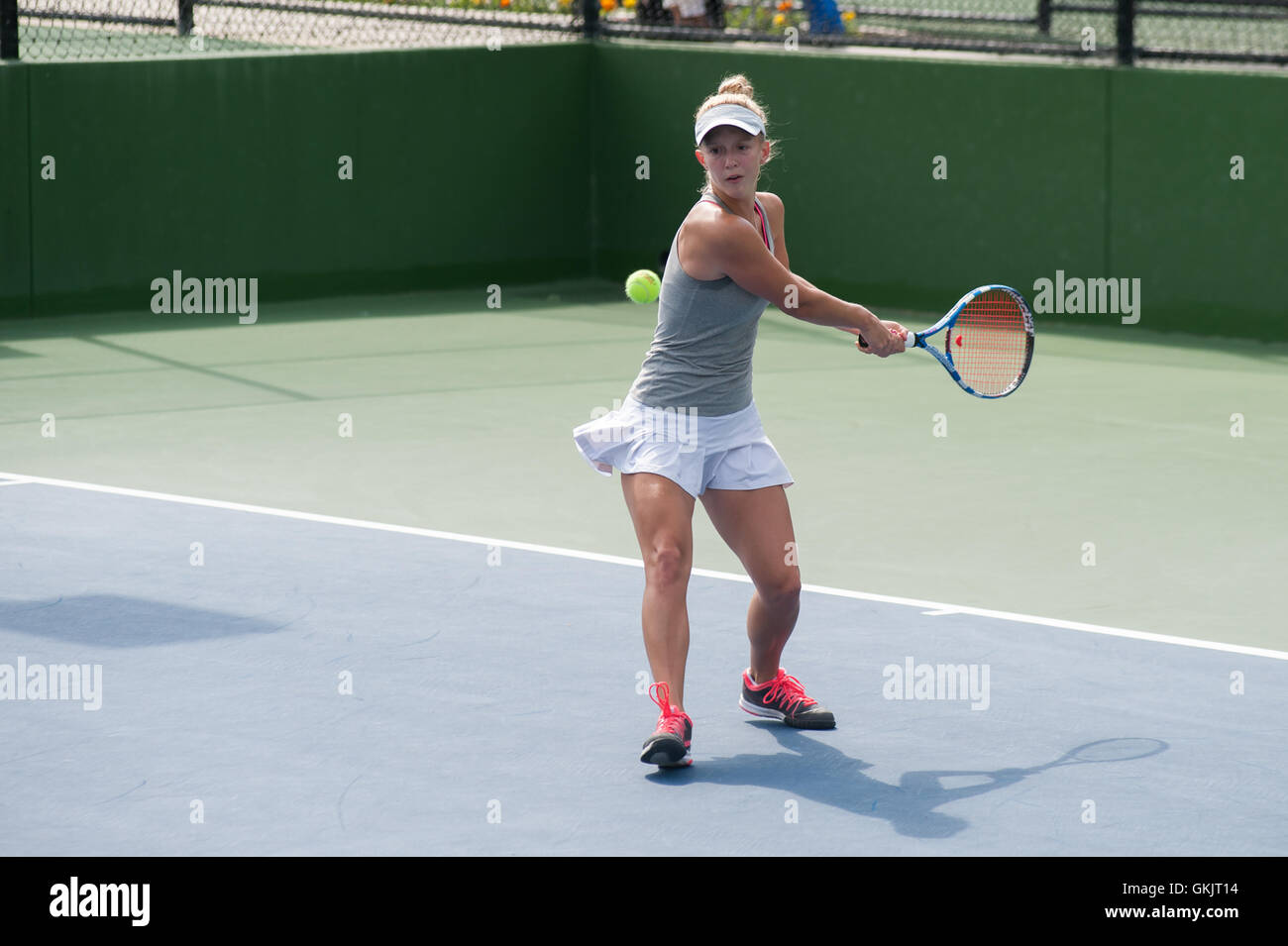 Female tennis athlete ready to hit a two handed backhand - Stock Image