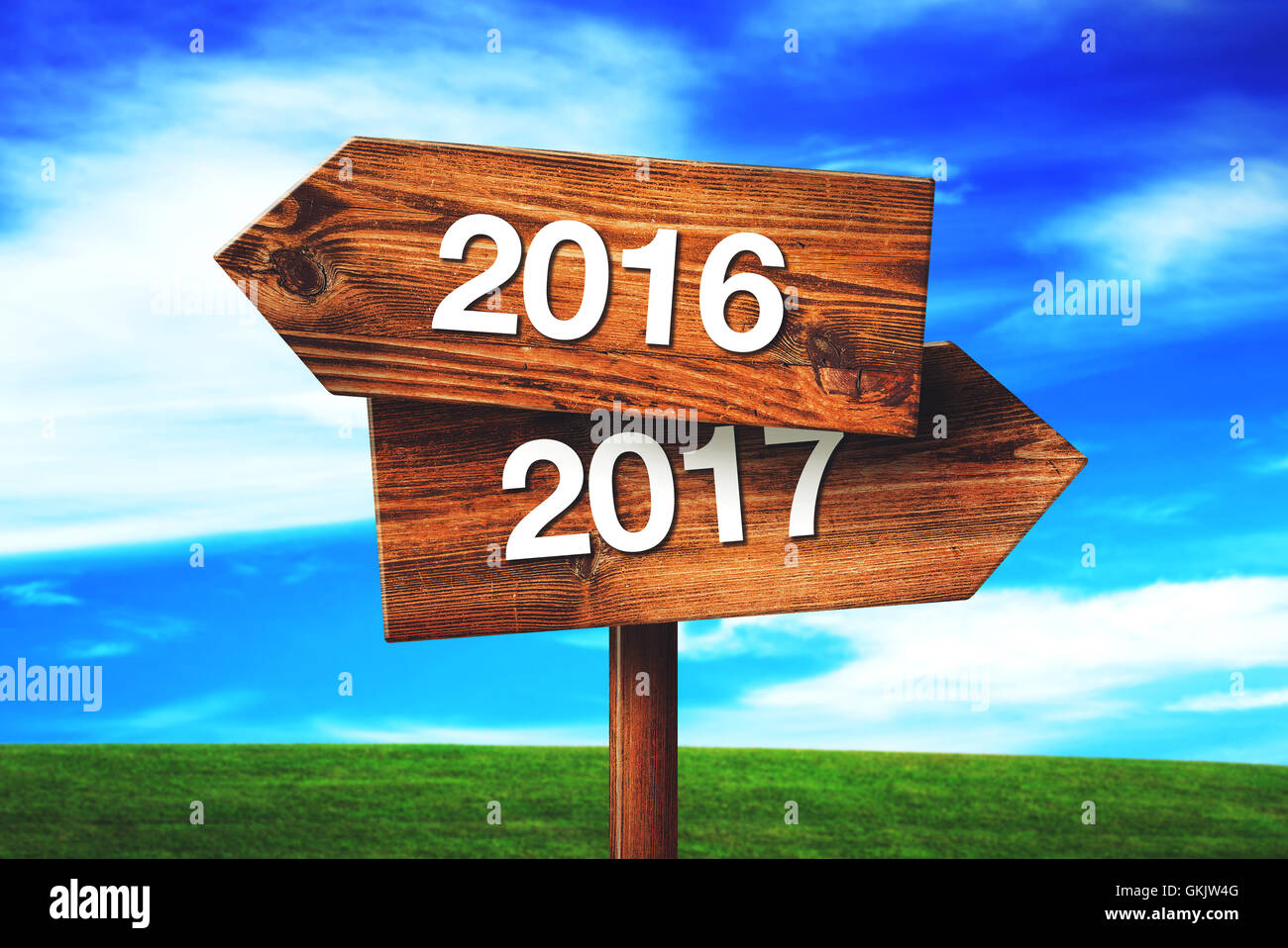 2016 and 2017 crossroads direction signs against blue sky - Stock Image