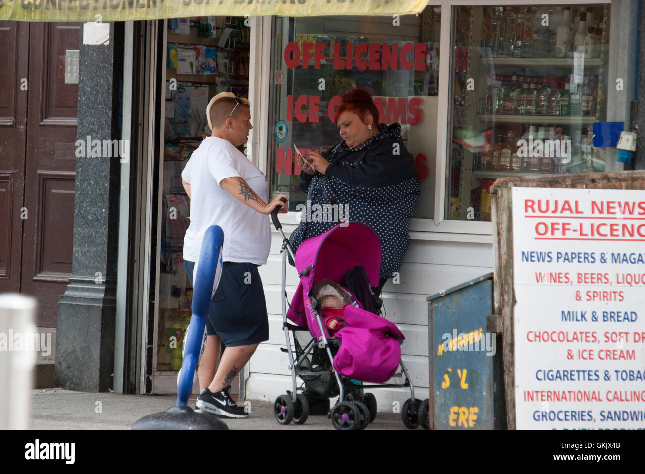 Two females with baby outside off licence, and newsagent, with scratch card Clacton Essex - Stock Image