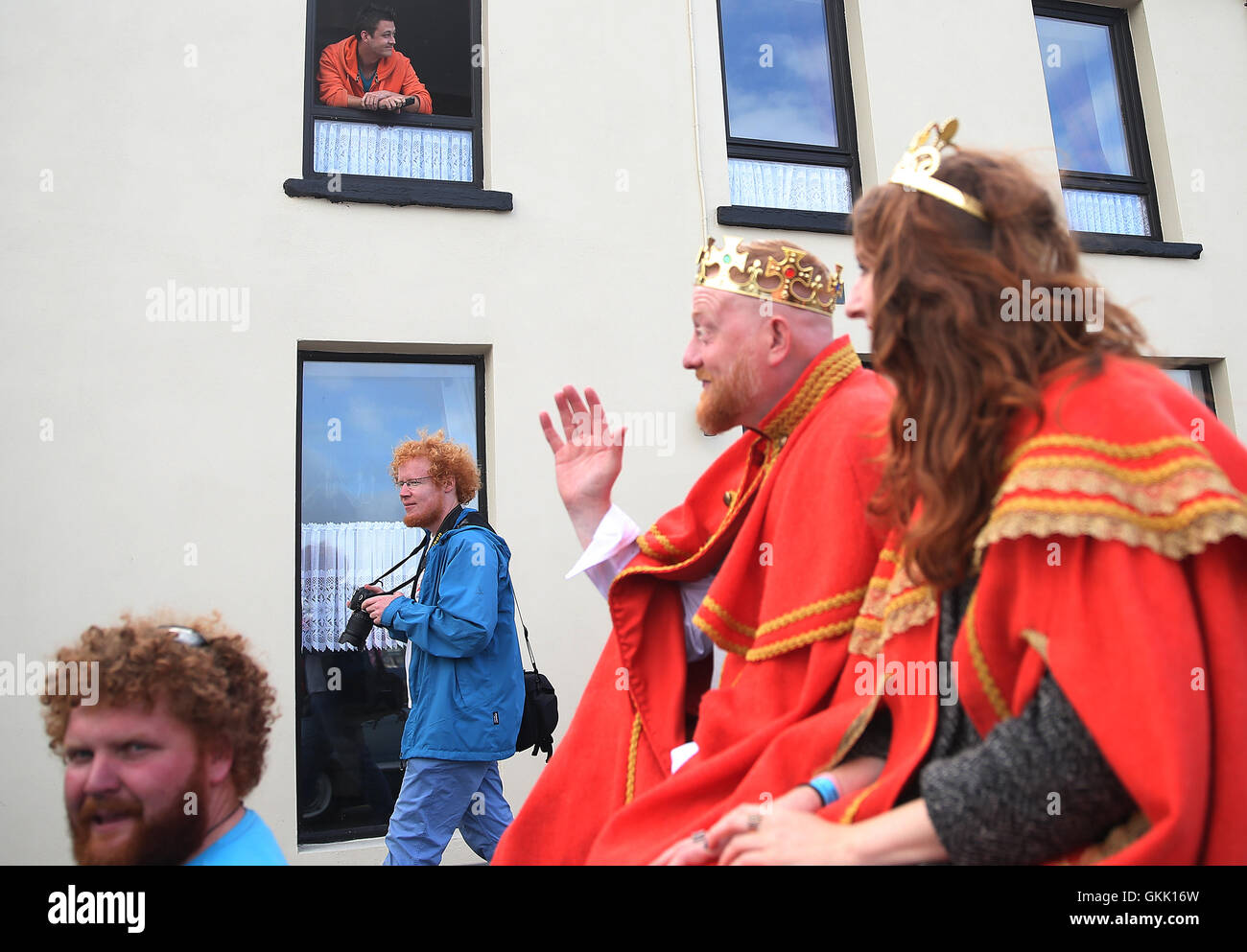 A man watches from an upstairs window as the newly crowned 'King and Queen of the Redheads' Alan O'Neill - Stock Image