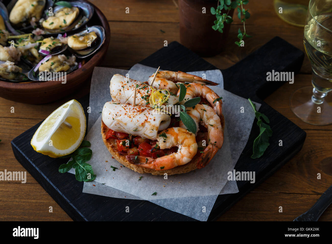 Tapas with shrimp and squid on wooden board, from top. Stock Photo