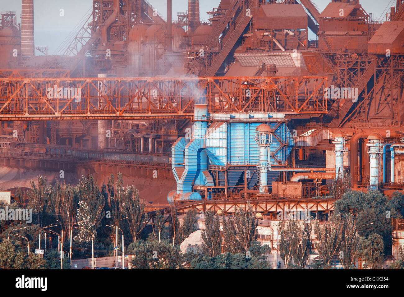 Industrial buildings . Steel factory at sunset. Pipes with smoke. Metallurgical plant. steelworks, iron works. Heavy industry in Stock Photo