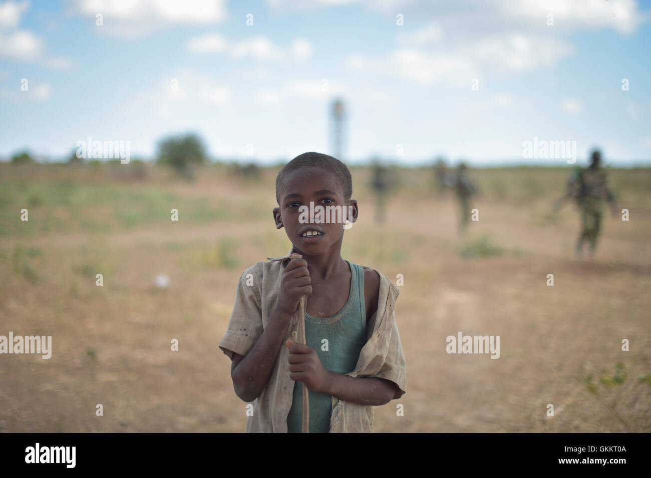 A young boy poses for the camera as Burundian trooops, part of the Afrian Union Mission in Somalia, patrol the countrside Stock Photo
