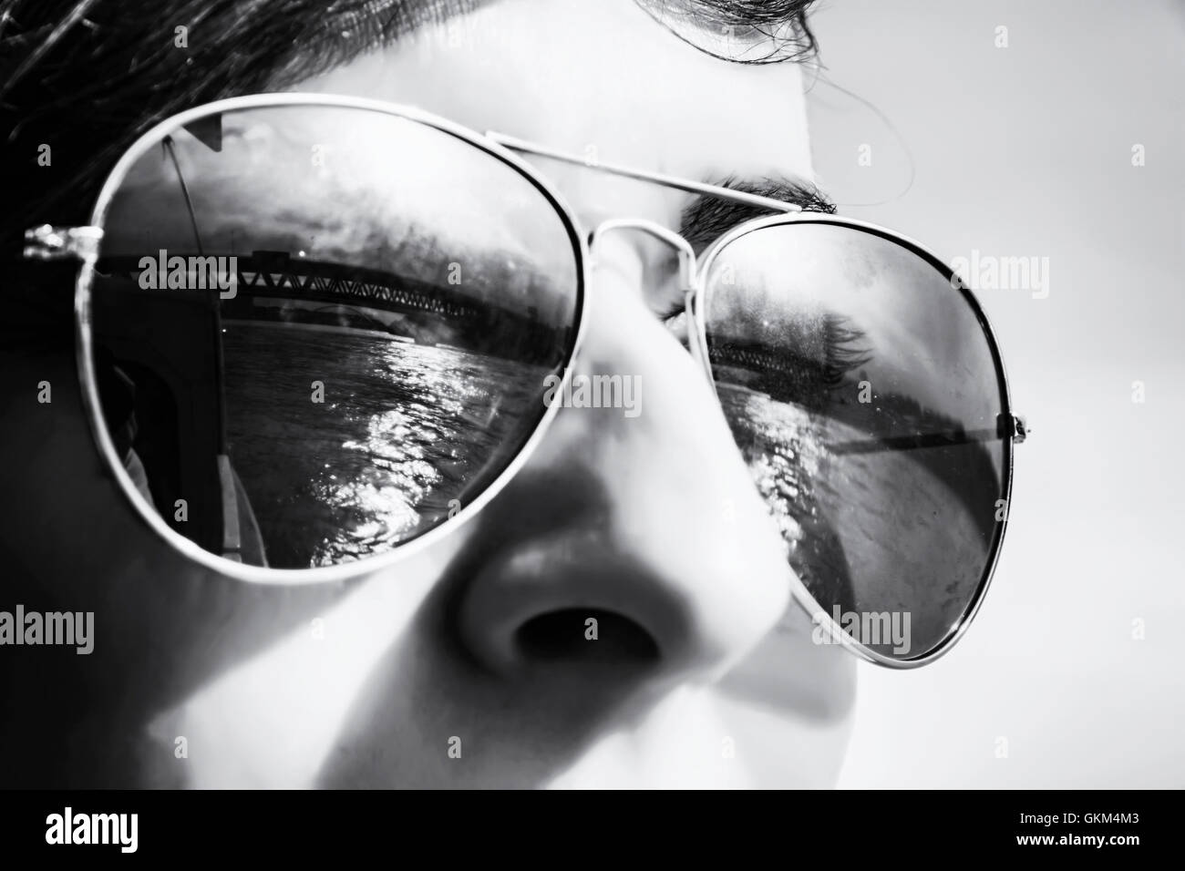 Teenage boy with mirroring bridge in sunglasses. Summer theme. Youngster portrait. Black and white photo. Stock Photo