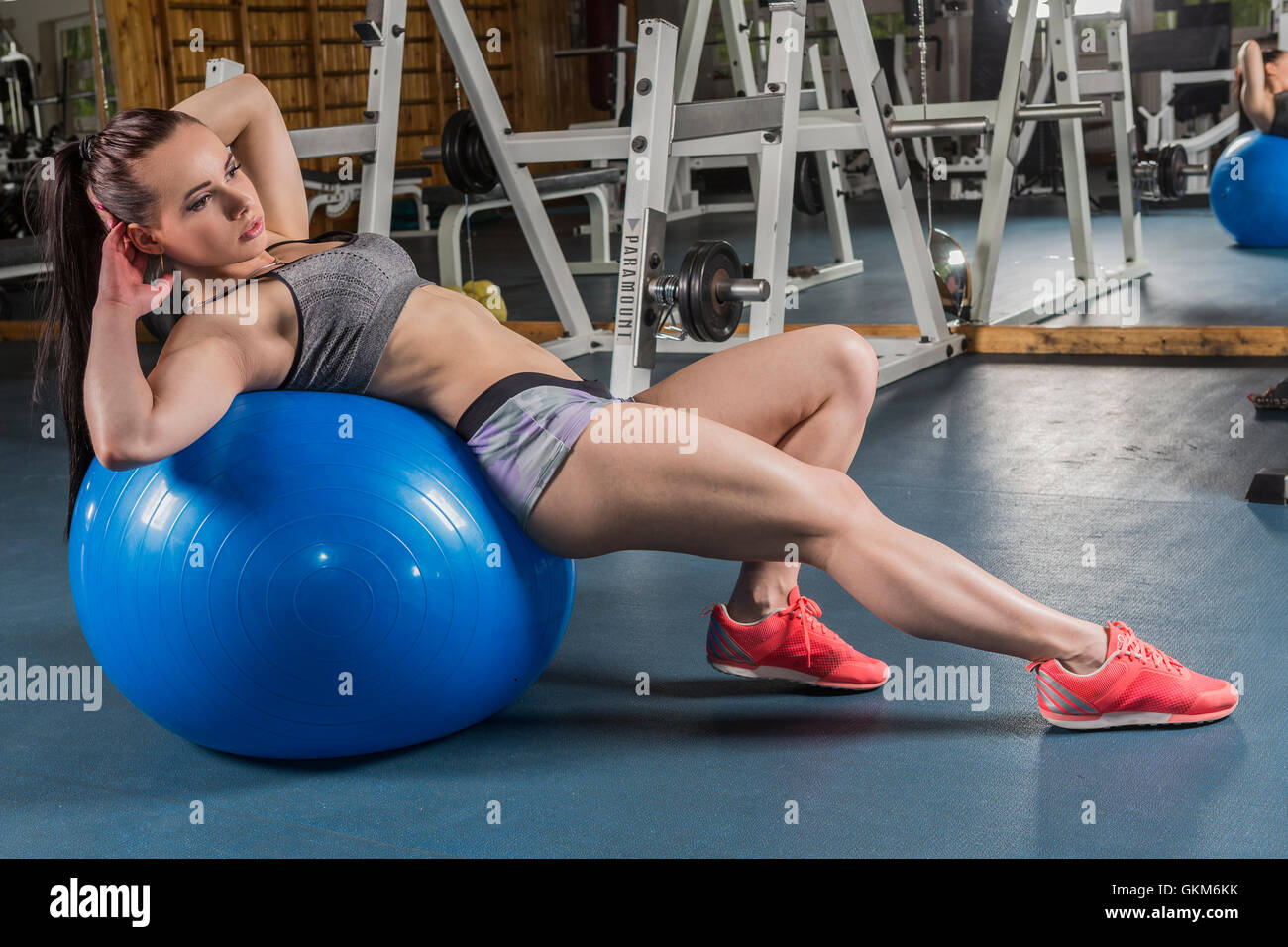 A muscular young women working out (or exercising) in a gym with an exercise ball - Stock Image