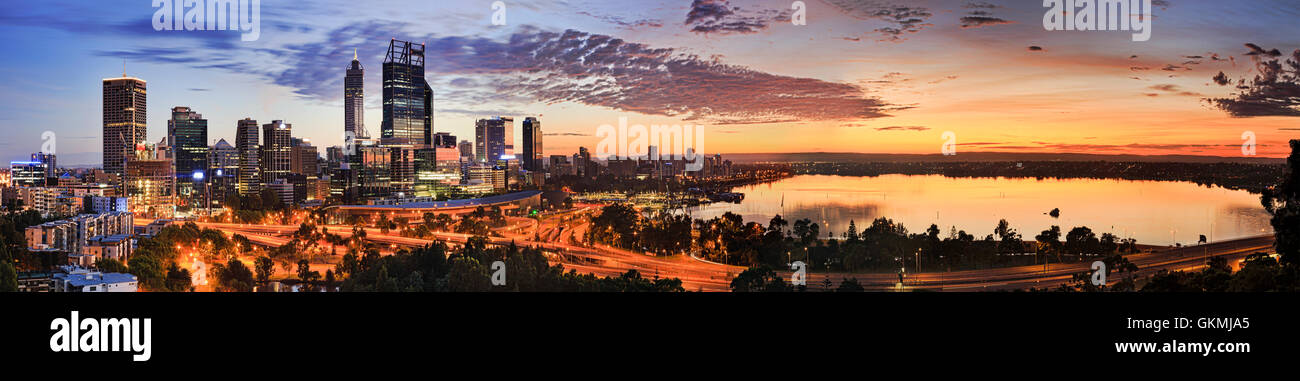 Wide panorama of Perth city CBD as seen from Kings Park lookout at sunrise. Rising orange sun reflects in still - Stock Image