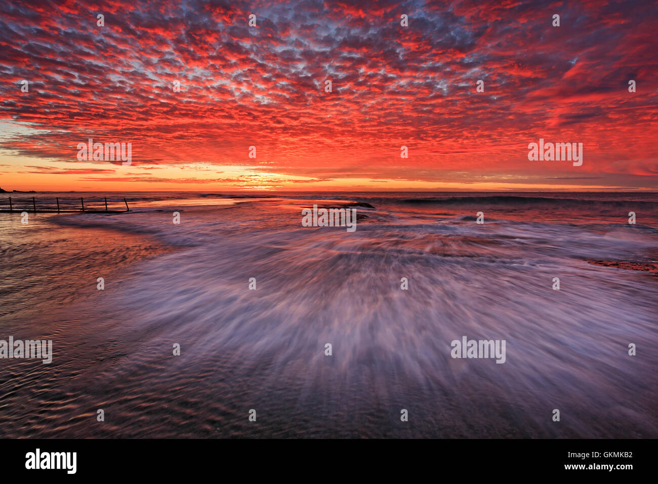 BLurred quick wave at golden hour over flat rocky seabed around rock pool of Mona Vale beach in Sydney. - Stock Image