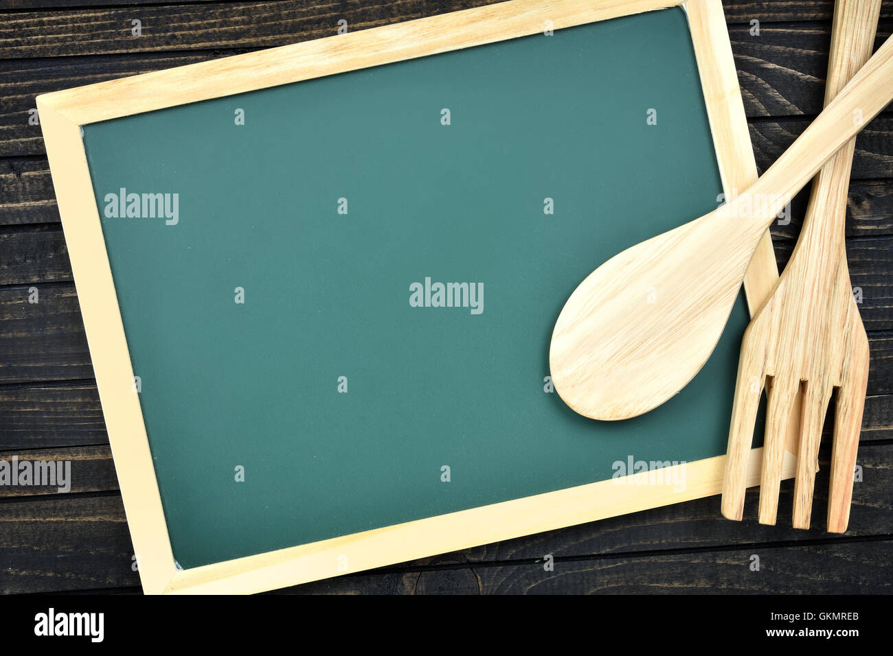 Kitchen utensils and green board on wooden table Stock Photo ...