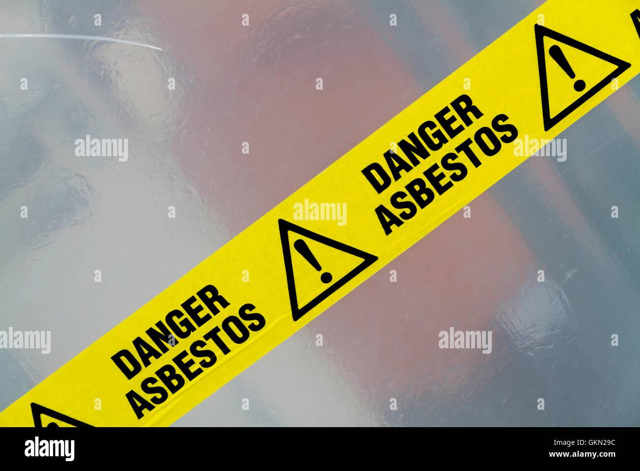 Danger Asbestos yellow warning tape close up - Stock Image