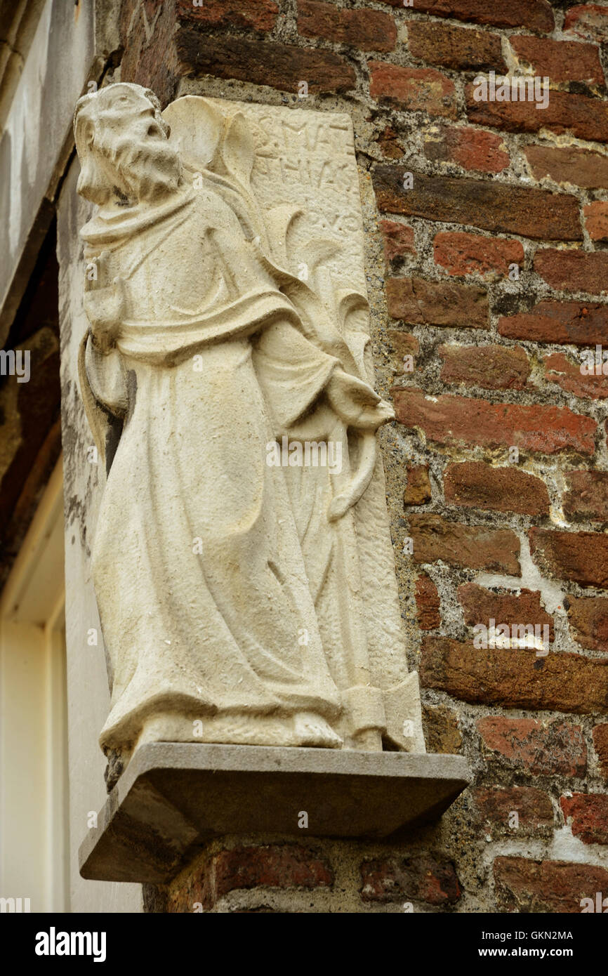 Small stone sculpture of St Mathias, on  corner of building next to the St Mathias Church, which is located just - Stock Image