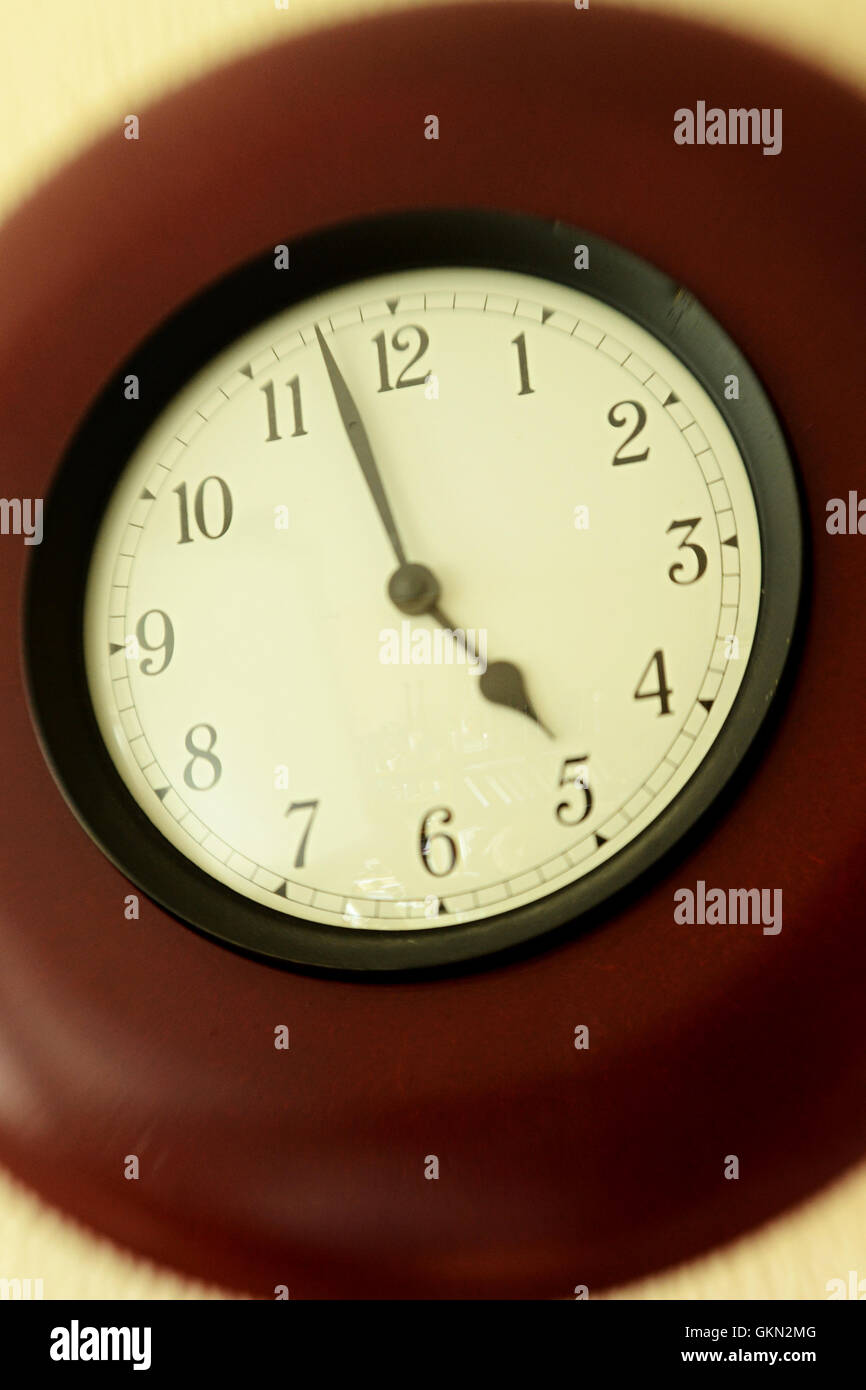 It's almost 5:00 - time to go home - quitting time. Clock hanging on wall. Taken with LensBaby for selective focus. Stock Photo