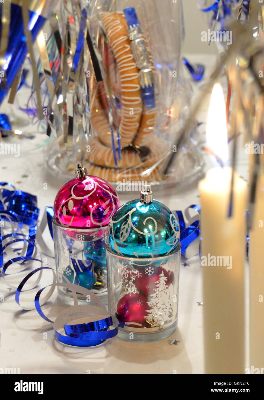A New Year's Eve decorated table with to candles. - Stock Image