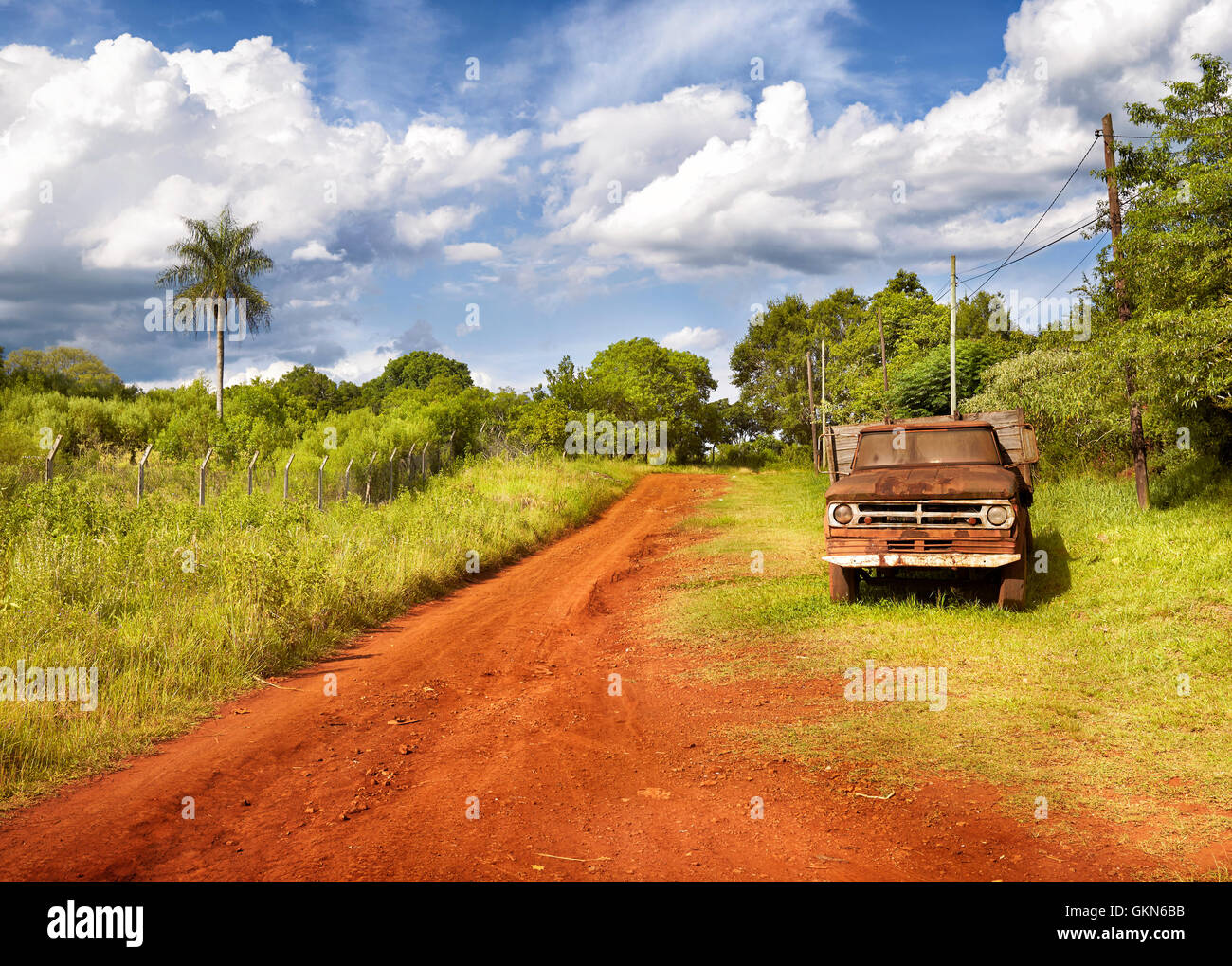 Red soil road and old abandoned truck. Landscape of Parana Misiones Province of Argentina. countryside.  Rural Landscape. - Stock Image