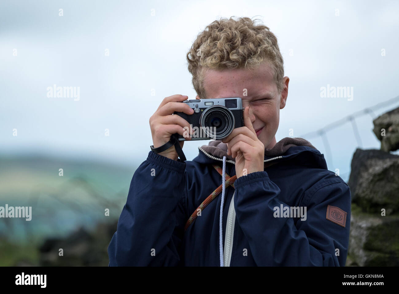 A young blonde haired boy taking a photo with a vintage camera - Stock Image