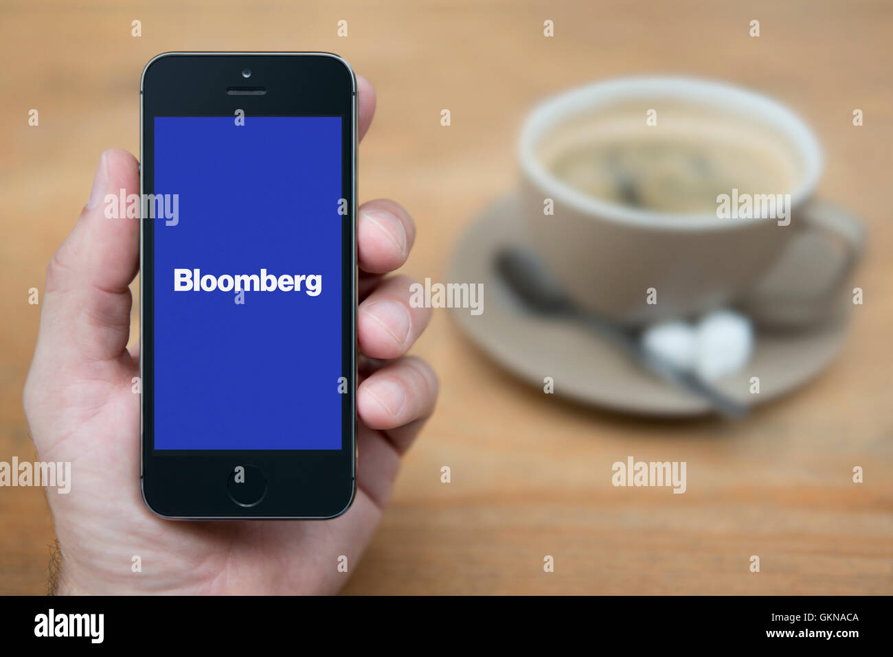 A man looks at his iPhone which displays the Bloomberg logo, while sat with a cup of coffee (Editorial use only). - Stock Image