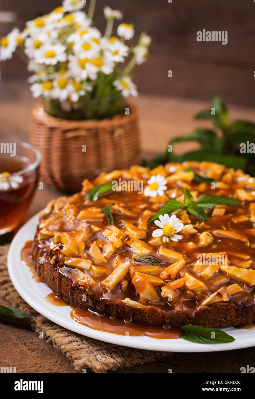 Apple pie with caramel sauce on a wooden background - Stock Image