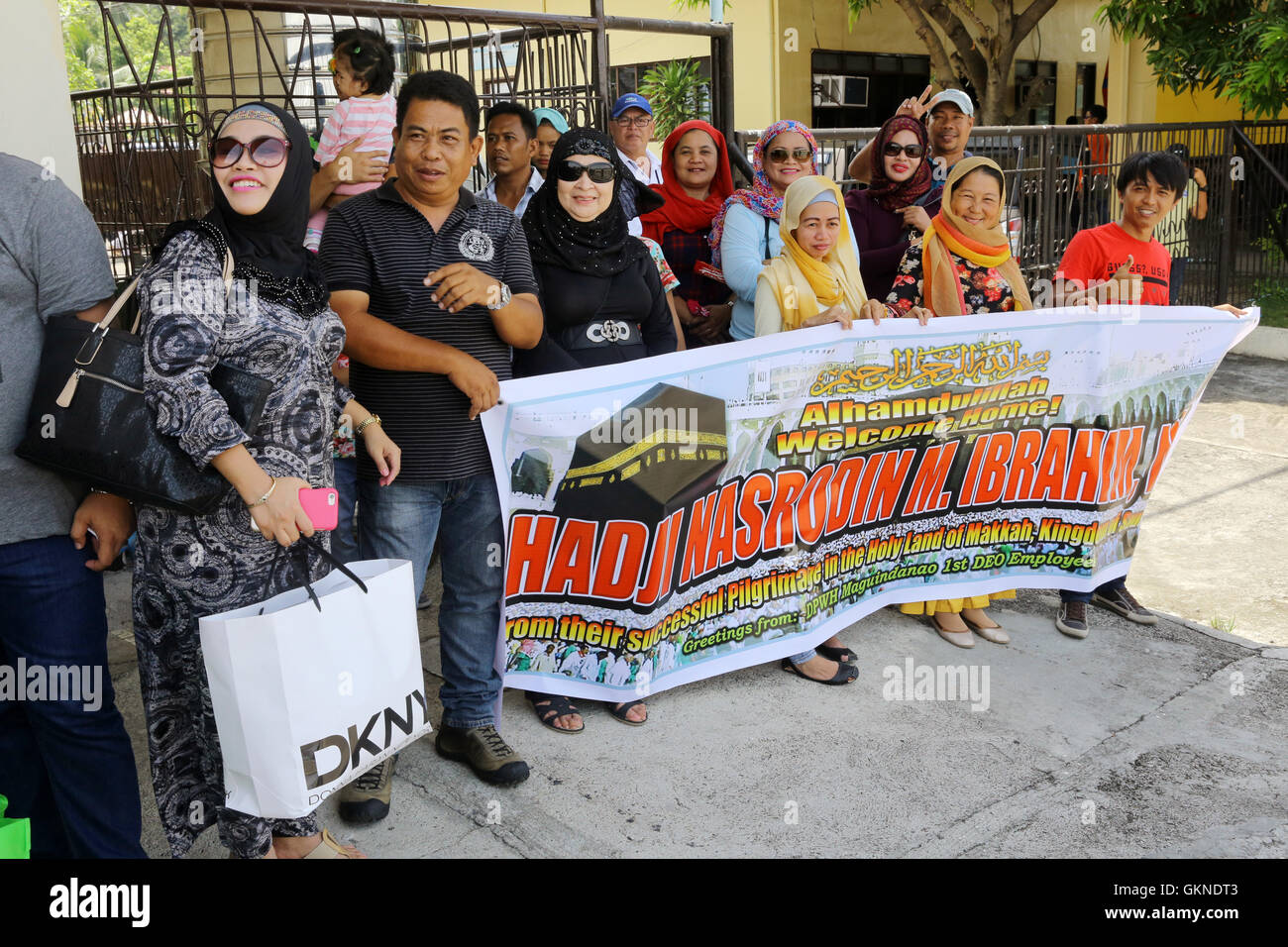 Relatives with a placard greet returnees from their pilgrimage to Mecca at the airport in Cotabato, Mindanao, Philippines - Stock Image