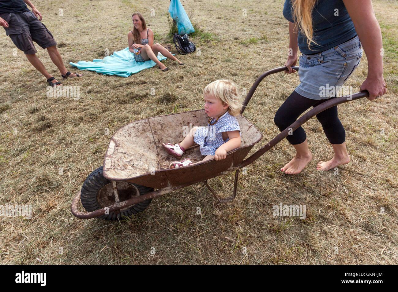 Woman carry a baby in a garden wheelbarrow, Czech Republic - Stock Image