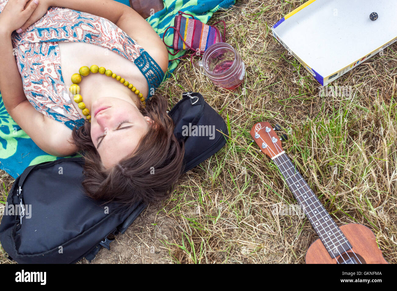 Girl with green beads on her neck lying on a summer meadow, Czech Republic - Stock Image
