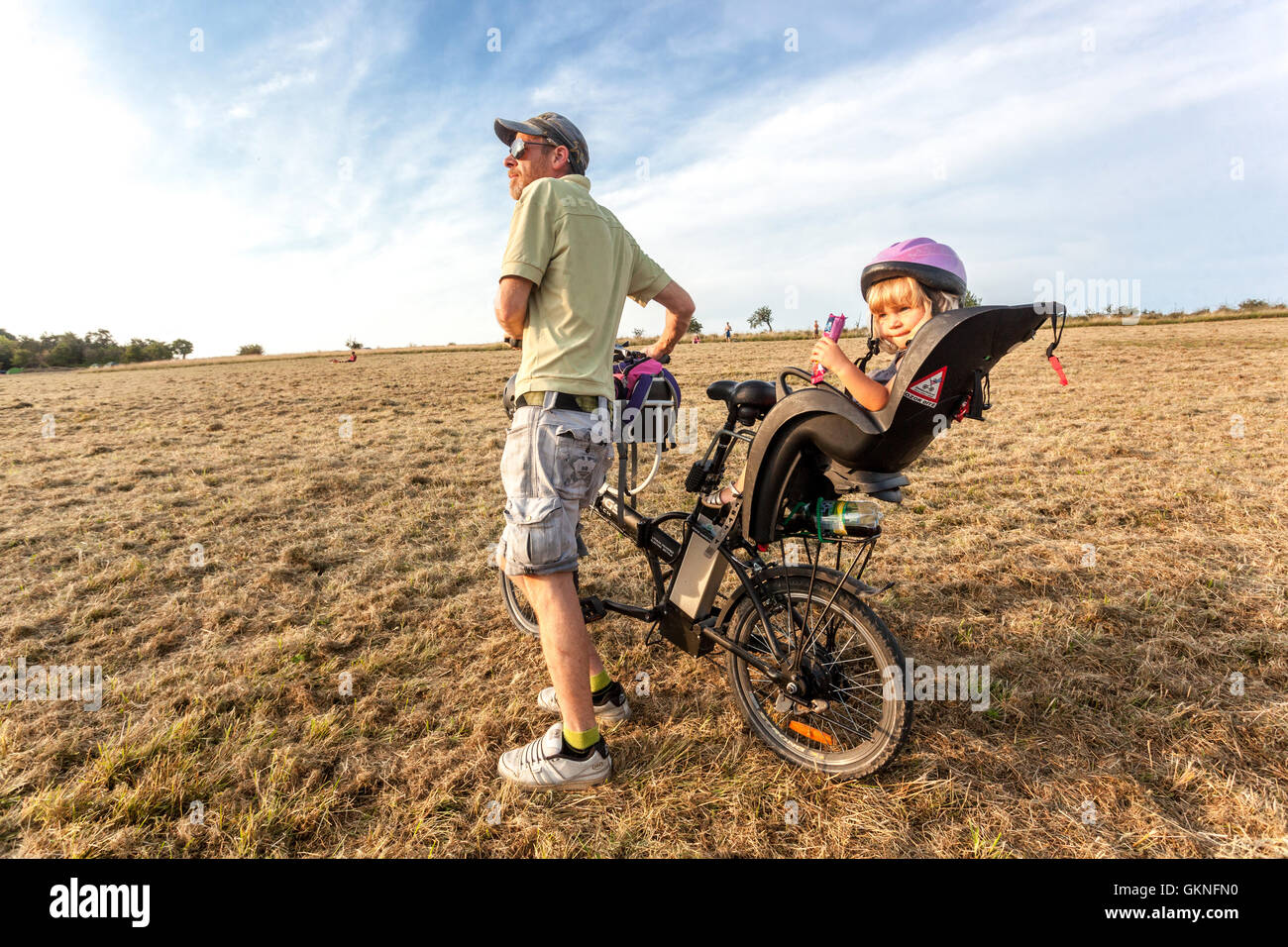Father and his beloved daughter in a summer meadow on a bicycle in a child seat, Czech Republic - Stock Image