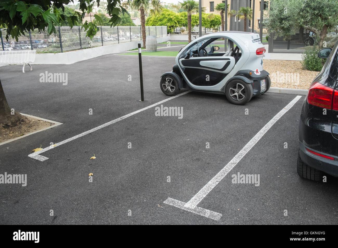Small micro car a Renault Twizy electric car badly parked,or blatantly ignoring marker lines in Limoux hospital Stock Photo