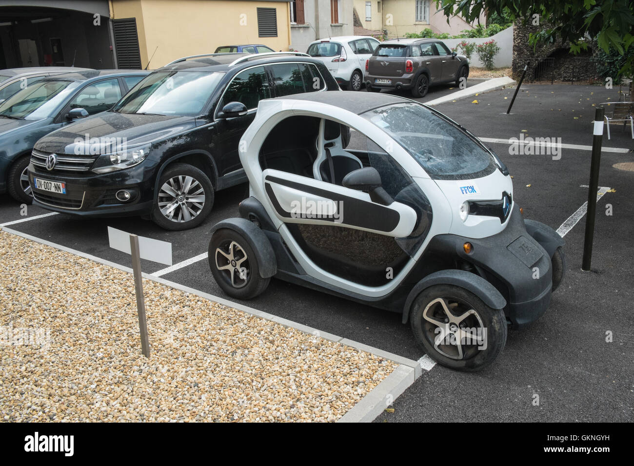 Small micro car a Renault Twizy electric car badly parked,or blatantly ignoring marker lines in Limoux hospital - Stock Image