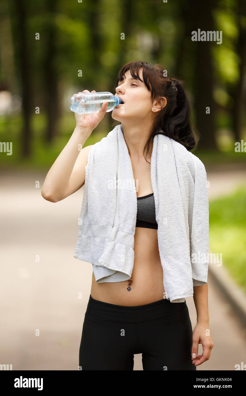 Attractive brunette sporty woman drinking water after fitness in park Stock Photo