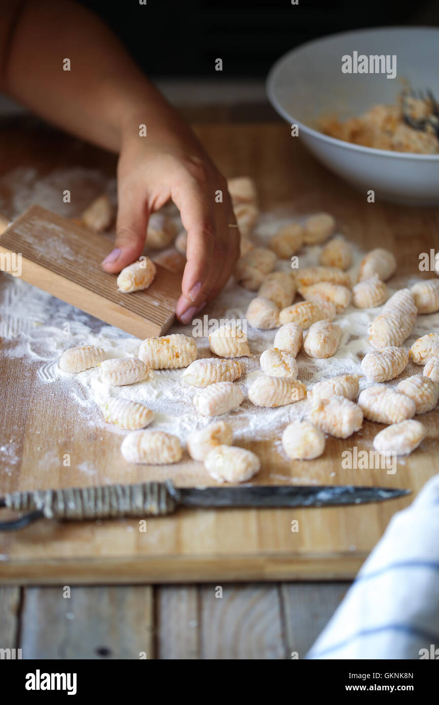 A woman rolls up the dough to prepare homemade gnocchi knife - Stock Image