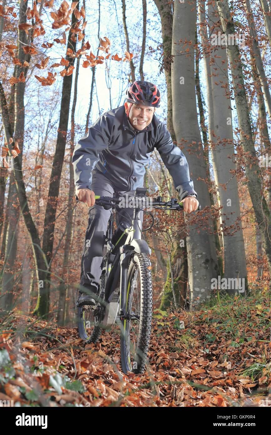 A Senior on Mountainbike in forest - Stock Image