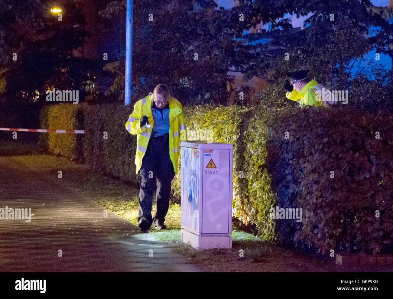 Berlin-Hellersdorf, Germany. 20th Aug, 2016. Two police officers search for clues at a crime scene in Berlin-Hellersdorf, - Stock Image