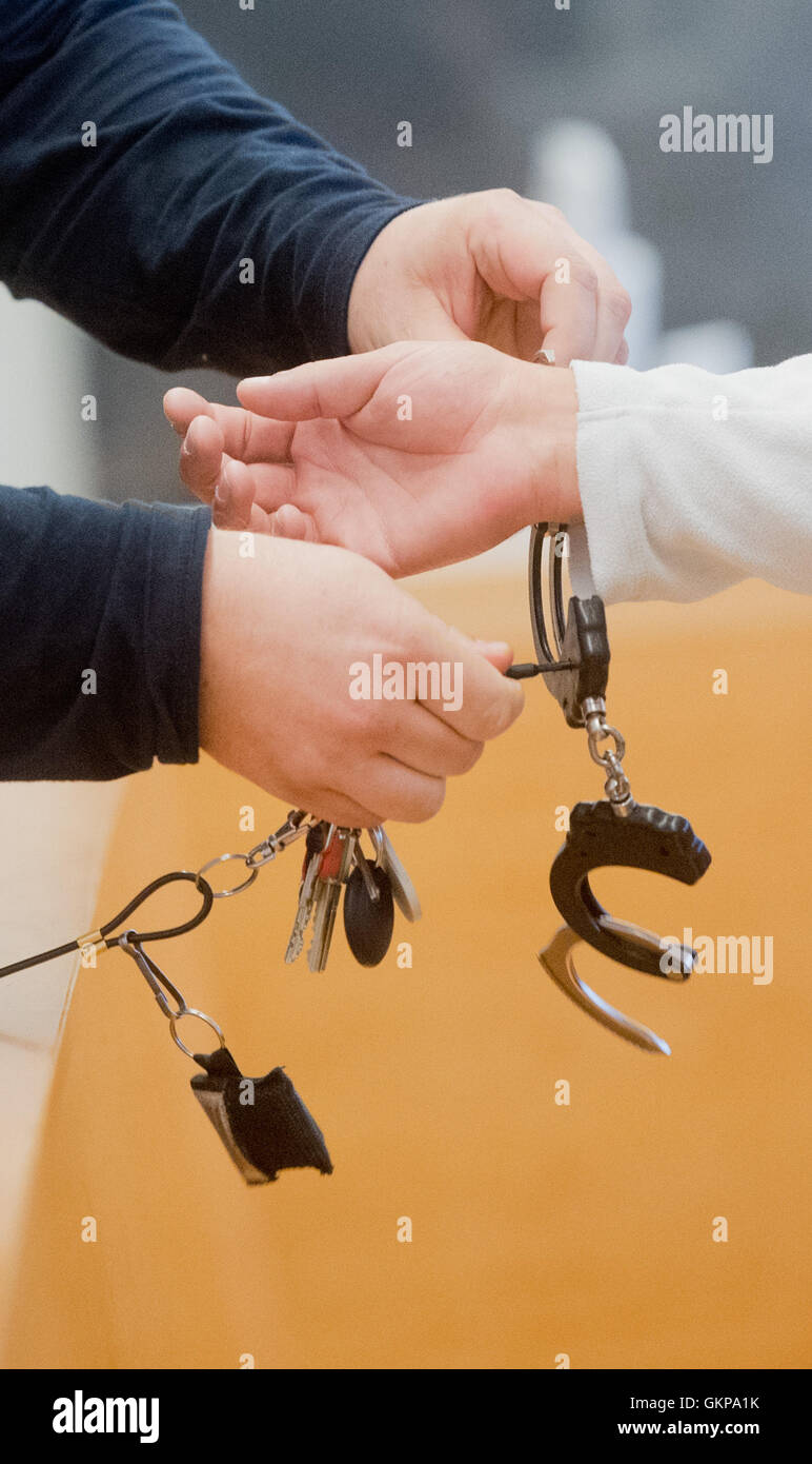 A judicial officer takes off the handcuffs of the accused Veljko M. at the Land court in Hannover, Germany, 22 August - Stock Image