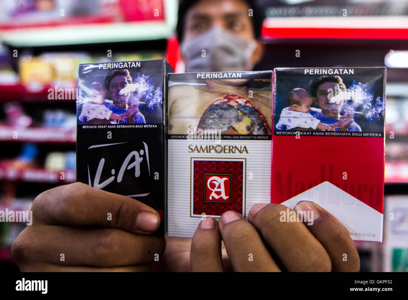 Medan, North Sumatra, Indonesia. 23rd Aug, 2016. A vendor holds packs of cigarettes to show at a mini store in Medan - Stock Image