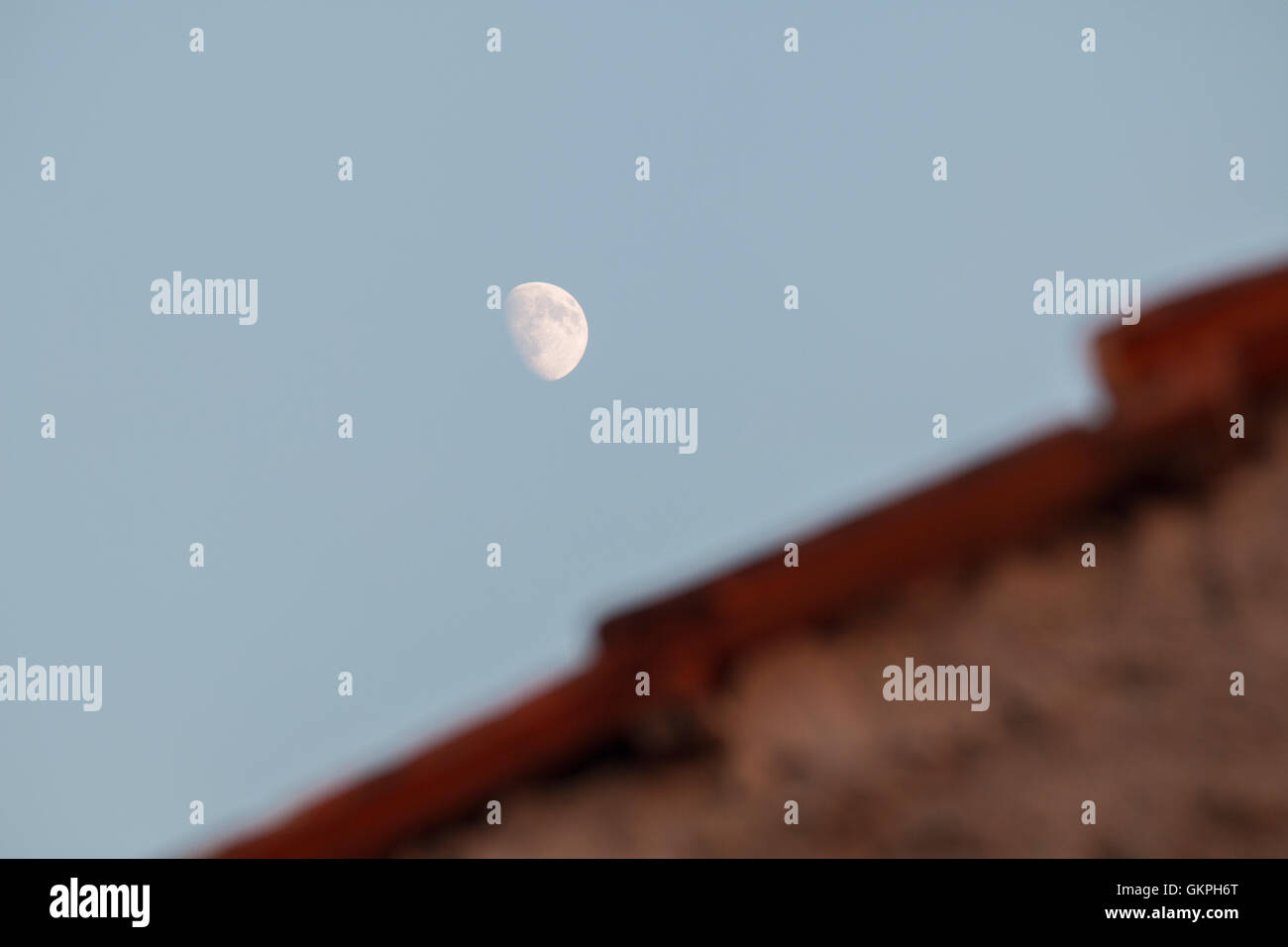 Moon over roof - Stock Image