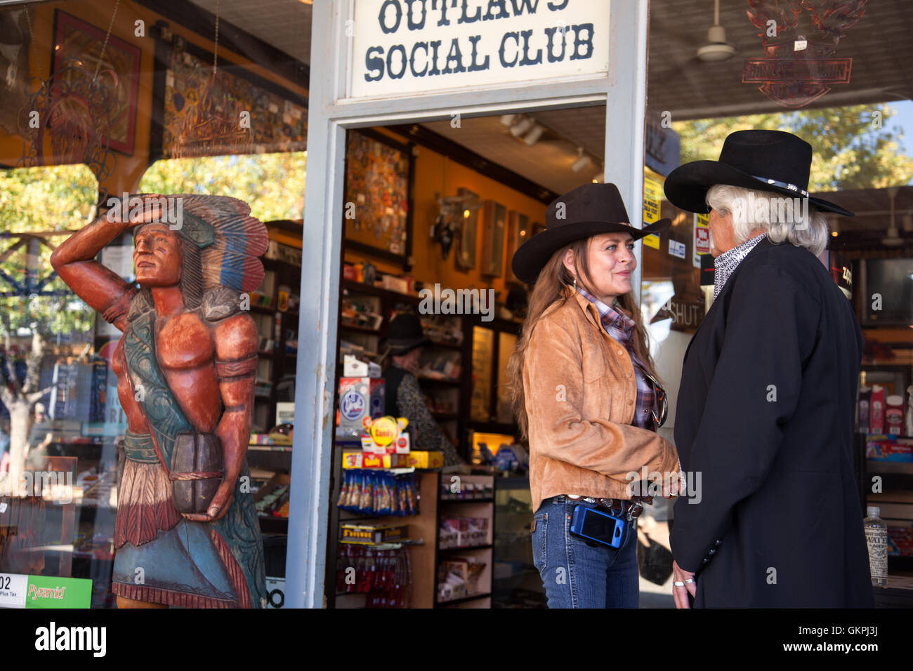 A couple stand outside the Outlaws Social Club store in Tombstone, Arizona. - Stock Image