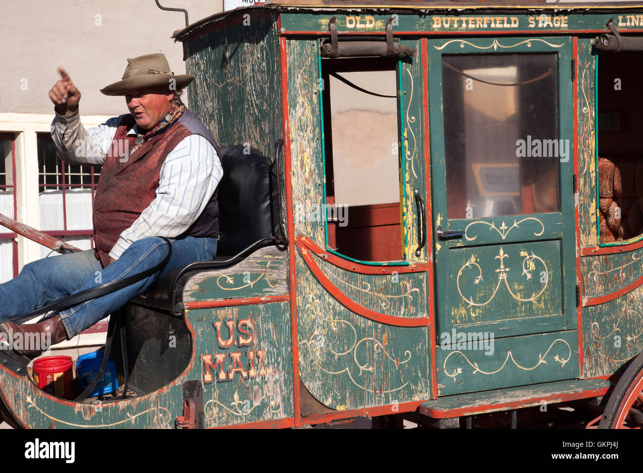A stage coach driver points during a conversation with tourists in Tombstone, Arizona. - Stock Image