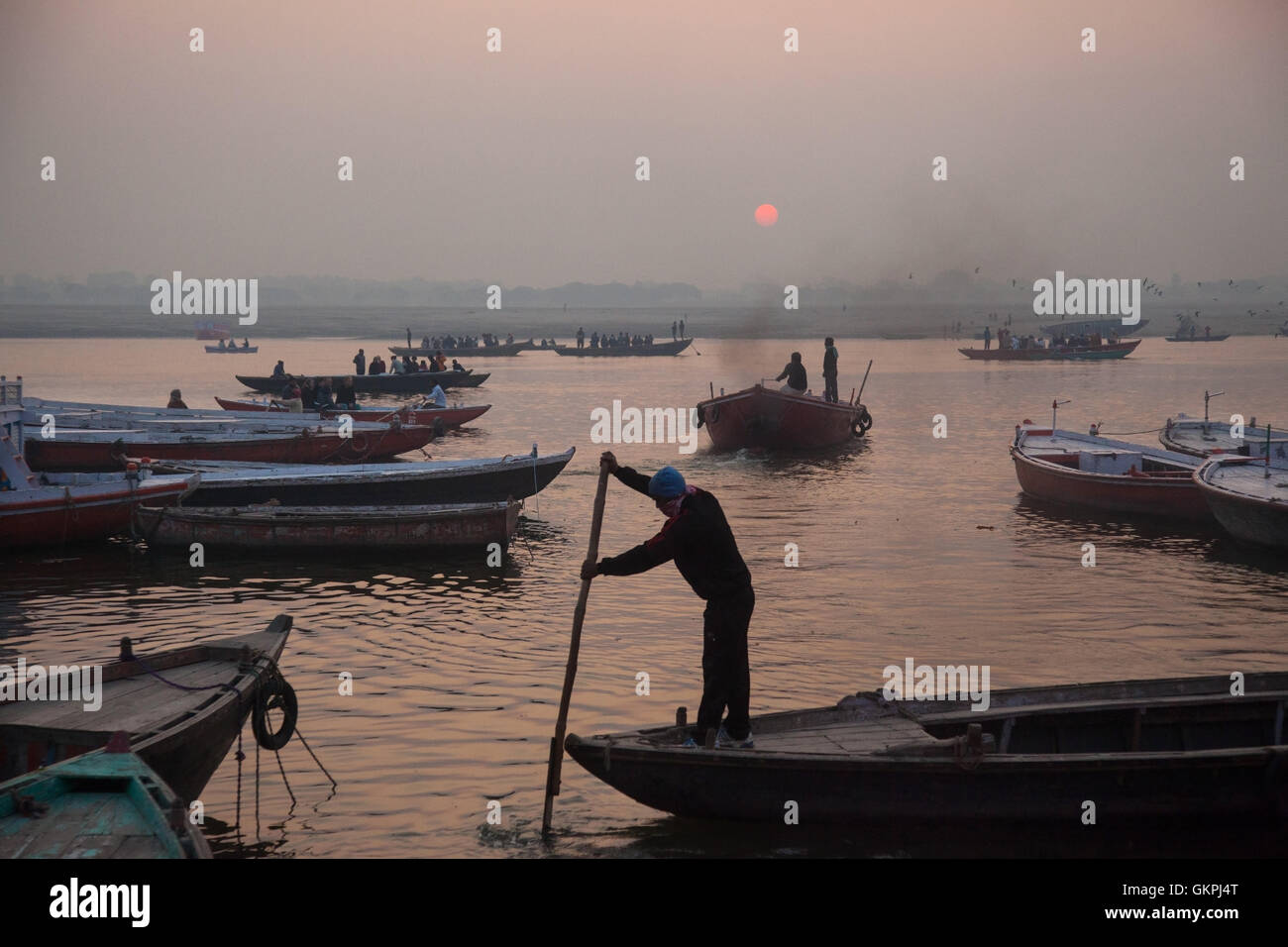 A boatman navigates his wooden boat as the sun rises over the Ganges River in Varanasi, India. - Stock Image