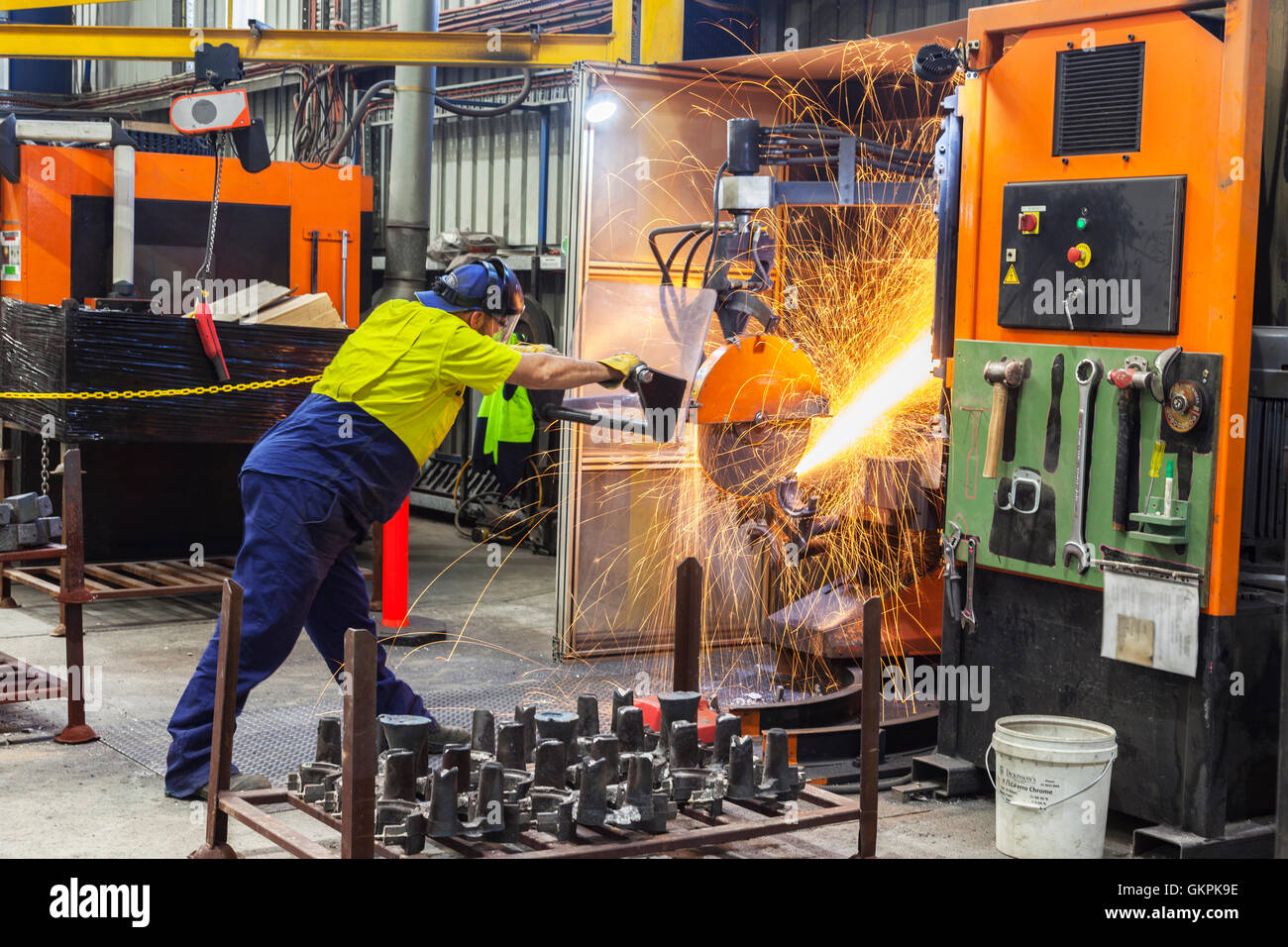 workman grinding and cutting away cast metal components from its 'casting' tree. - Stock Image