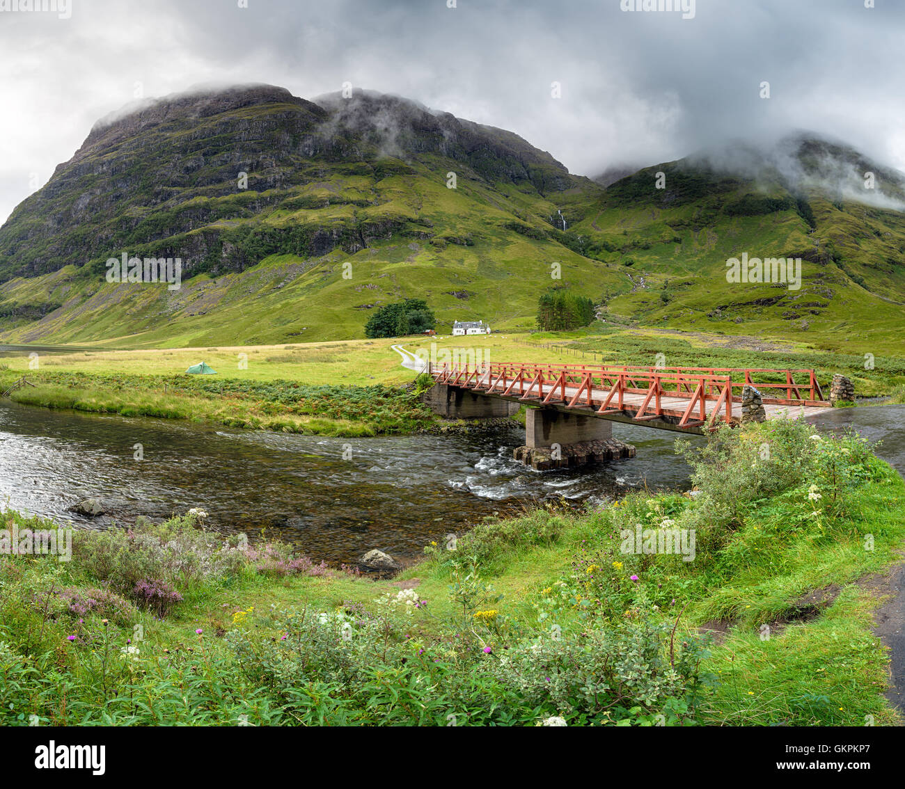 A bridge over the river Coe with Achnambeithach cottage nestled under the mountains - Stock Image