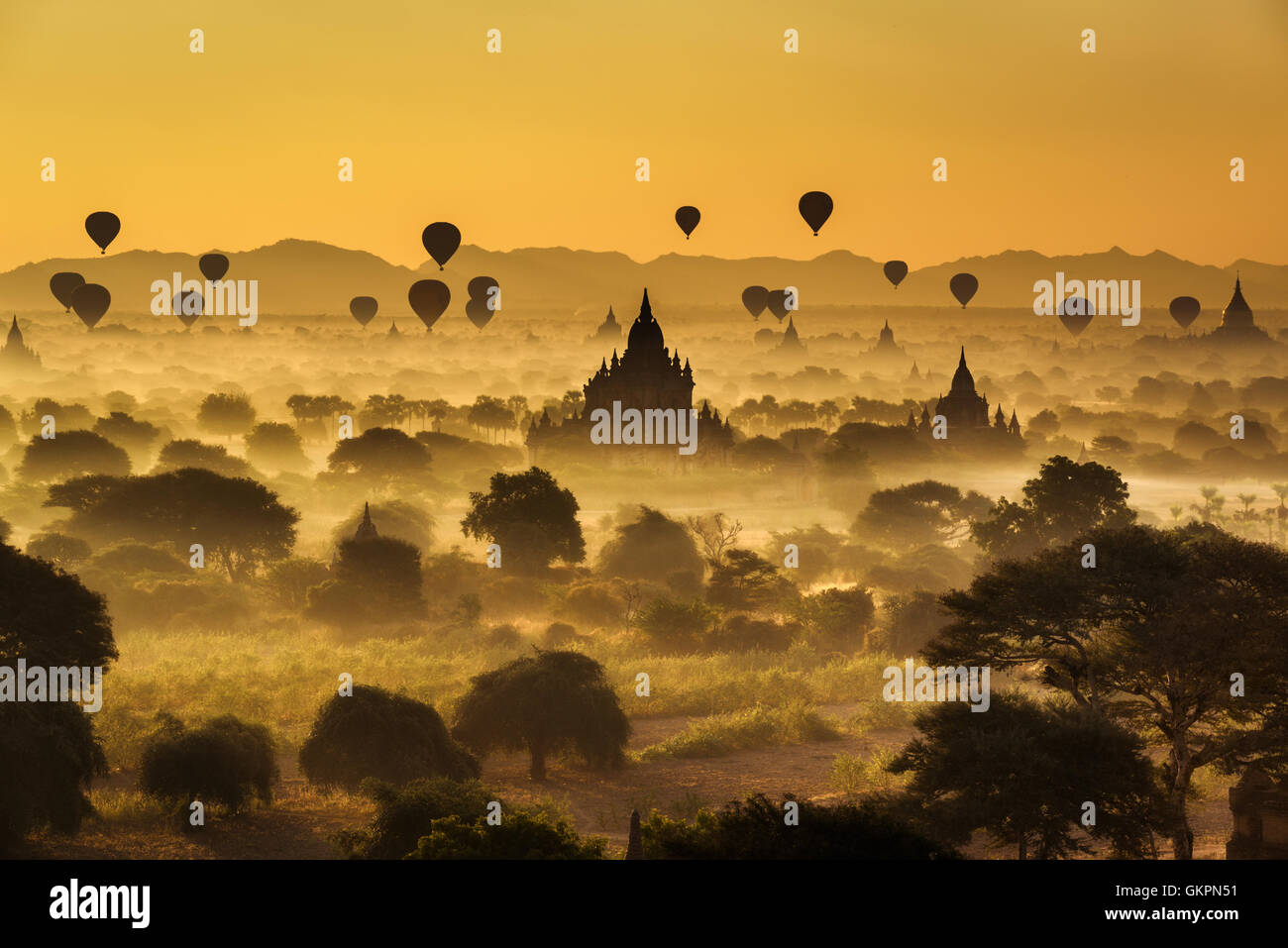 Scenic sunrise with many hot air balloons above Bagan in Myanmar - Stock Image