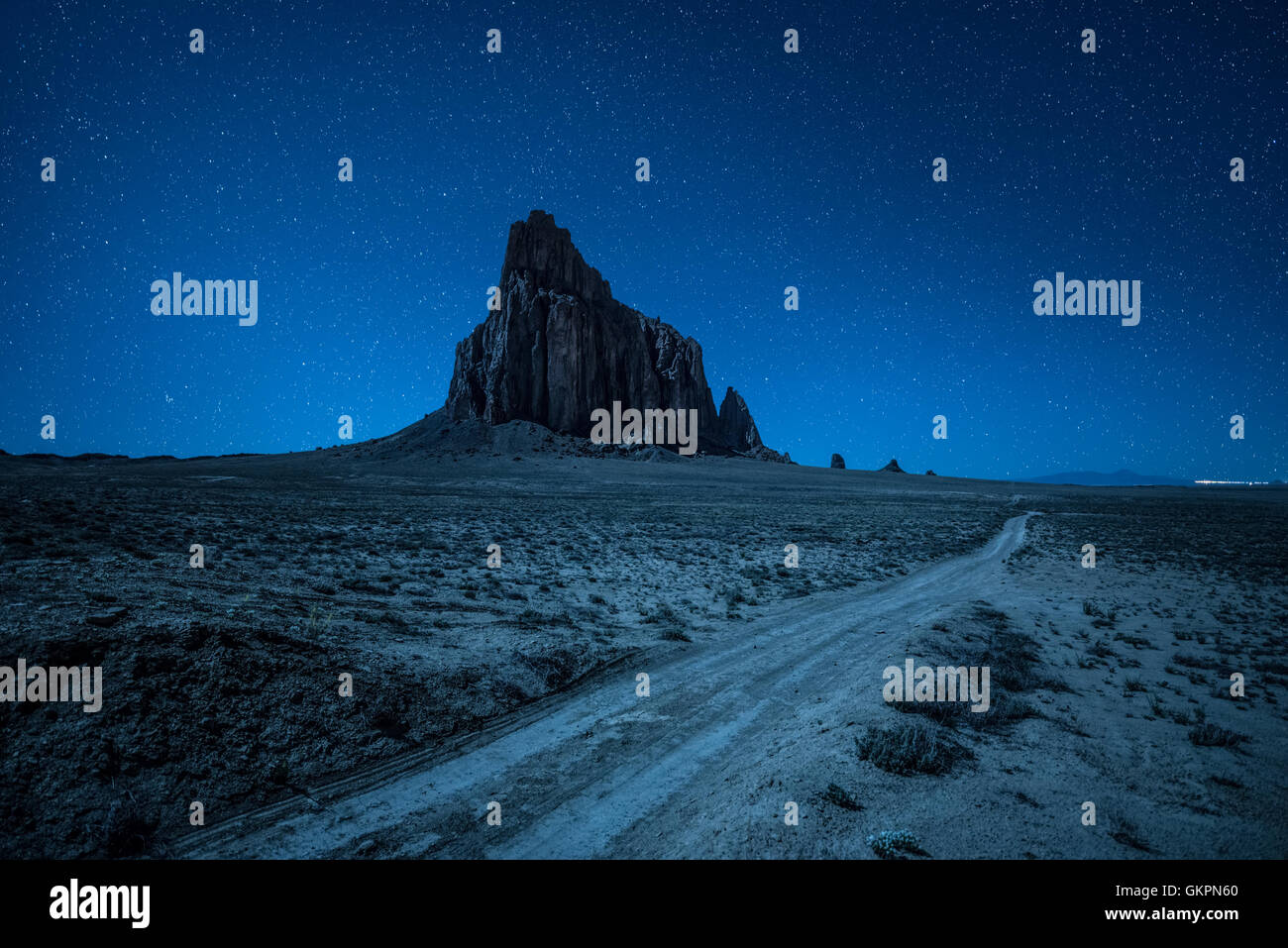 Night sky with many stars above Shiprock and a dirt road - Stock Image